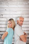 Unhappy couple not speaking to each other against wooden planks