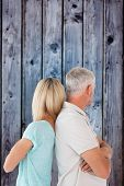 Unhappy couple not speaking to each other against grey wooden planks