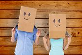 stock photo of emoticons  - Couple wearing emoticon face boxes on their heads against wooden planks background - JPG