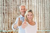 Smiling couple showing thumbs up together against faded pine wooden planks