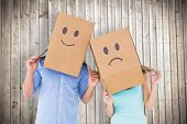 Couple wearing sad face boxes on their heads against wooden planks background