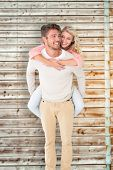 Handsome man giving piggy back to his girlfriend against faded pine wooden planks