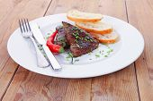 image of red meat  - fresh hot grilled beef meat steak served with red hot pepper and white bun slices on plate over wooden table - JPG