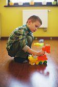Happy beautiful boy plays with blocks