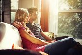 couple at home on couch watching tv with lens flare and artistic color toning to image