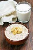 Oatmeal Porridge With Banana Slices And Glass Of Milk