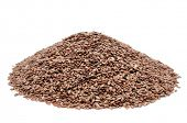 a pile of brown flax seeds on a white background