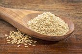 gold flax meal on a wooden spoon with seeds against a grunge wood