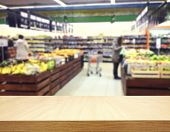 Brown table and on background blured supermarket. Empty space for you design