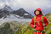 Alps Hiking - Asian hiker woman in Switzerland on trek in mountains with backpack living a healthy active lifestyle. Hiker girl on nature landscape hike in Urner Alps, Berne, Swiss alps, Switzerland.