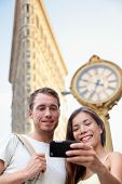 Travel couple taking selfie in New York City NYC, USA. Tourists holding smartphone to photograph self-portrait in front of famous Flatiron building downtown in summer.