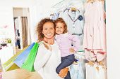 Smiling mother holds shopping bags with daughter