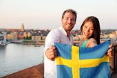Swedish people holding Sweden flag in Stockholm. Candid fresh Scandinavian man and Asian woman looking at old town cityscape sunset view from Monteliusvagen overlooking Gamla Stan, the old city.