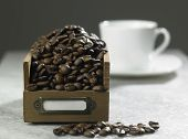 roasted coffee bean next to the cup