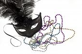 stock photo of debauchery  - Shiny gold purple blue and silver beads and Mardi Gras mask with feathers on a white background - JPG