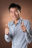 Young Chinese frank businessman give you an excellent gesture, closeup portrait in studio.