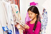 Cute Asian girl with braid choosing clothes