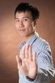 Young Chinese frank businessman give you an stop gesture, closeup portrait in studio.