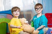 pic of home remedy  - kids brothers play doctor with plush toy at home - JPG