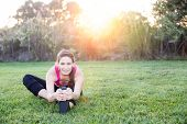 Young woman stretching at the park at sunset