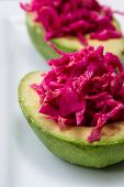 image of fermentation  - serving of fermented or cultured purple cabbage paired with an avocado on a white plate - JPG