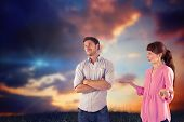 Woman arguing with uncaring man against blue and orange sky with clouds