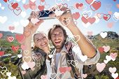 Hiking couple standing on mountain terrain taking a selfie against valentines heart design