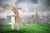 Happy couple posing in trench coats against cloudy sky over city