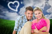Attractive young couple sitting holding heart cushion against green field under blue sky
