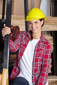 Portrait of confident female engineer wearing hardhat in workshop