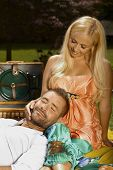 Relaxed smiling casual man laying in lap of happy romantic blonde woman at picnic, outdoor.