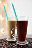 Black coffee and coffee with milk in glasses with drinking straw