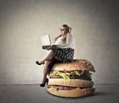 stock photo of grease  - Chubby woman sitting on a giant hamburger  - JPG
