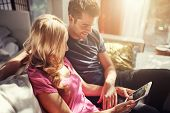 attractive couple using tablet together on futon h at home