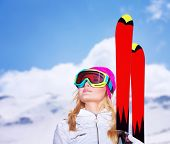 Closeup portrait of cute skier girl looking up on the sky, wearing special sportive mask, active lifestyle, enjoying winter vacation concept