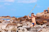 picture of aborigines  - cute boy with bamboo spear pretends like he is aborigine on desert island - JPG