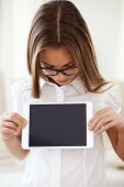 8 years old school girl wearing glasses holding tablet pc