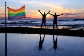 stock photo of gay pride  - Silhouette of two men at sunset with a gay pride flag in the foreground - JPG