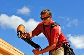 stock photo of top-gun  - Building contractor worker with a air nail gun nailer working on the corner of the top plate of the first floor walls on a new home construciton project - JPG