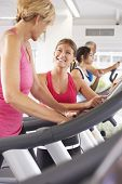 image of encouraging  - Woman On Running Machine In Gym Encouraged By Personal Trainer - JPG