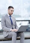 business, education, technology and people concept - businessman working with laptop computer on cit poster