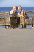 picture of couple sitting beach  - Senior Couple Sitting In Chairs Relaxing On Beach - JPG