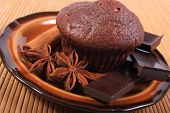 image of chocolate muffin  - Homemade delicious fresh baked chocolate muffins pieces of chocolate and star anise lying on plate - JPG