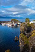 stock photo of fjord  - White fishing boat in the harbor pier fishing village Arnastapi - JPG