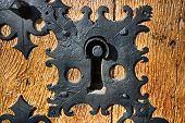stock photo of keyhole  - large iron ancient keyhole close-up on a wooden door of a medieval castle ** Note: Shallow depth of field - JPG