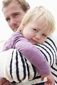 stock photo of cuddle  - Father Cuddling Young Daughter Outdoors - JPG