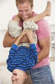 stock photo of upside  - Father Holding Son Upside Down At Home - JPG