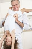 picture of upside  - Grandfather Holding Granddaughter Upside Down At Home - JPG