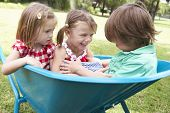 stock photo of three sisters  - Three Children Sitting In Wheelbarrow - JPG