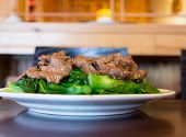foto of mongolian  - Mongolian beef over green vegetable on white plate reflecting on dark brown wood table with picture taken from a front angle - JPG